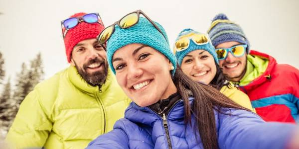 A family wearing winter gear and smiling at the camera