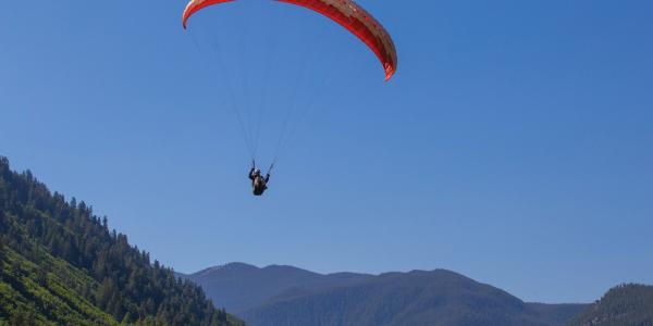 Paraglider surrounded by blue sky